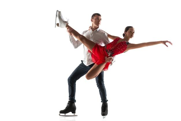 コピースペースと白いスタジオの壁に分離されたデュオフィギュアスケート。アクションとモーションの練習とトレーニングを行う2人のスポーツマン。優雅さと無重力に満ちています。動き、スポーツ、美しさの概念。