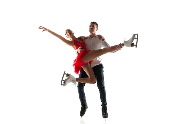 コピースペースで白い壁に分離されたデュオフィギュアスケート。アクションとモーションの練習とトレーニングを行う2人のスポーツマン。優雅さと無重力に満ちています。動き、スポーツ、美しさの概念。