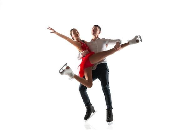 孤立したデュオフィギュアスケート。アクションとモーションの練習とトレーニングを行う2人のスポーツマン。優雅さと無重力に満ちています。動き、スポーツ、美しさの概念。
