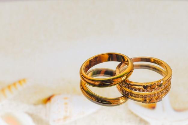 Дуэт золотое обручальное кольцо на цветном фоне.