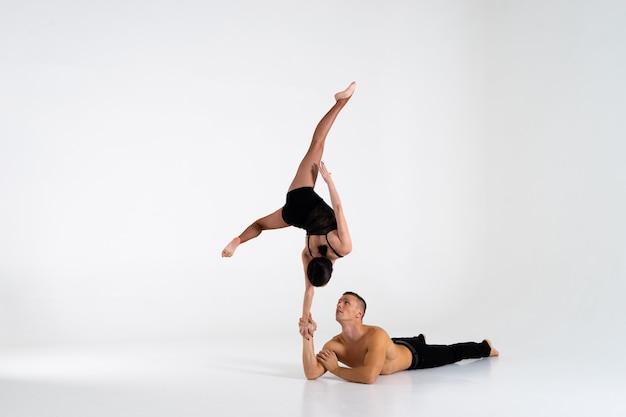 Дуэт акробатов мужского и женского пола, показывающий трюк из рук в руки, изолированный на белом