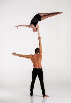 Дуэт мужских и женских акробатов показывает трюк из рук в руки