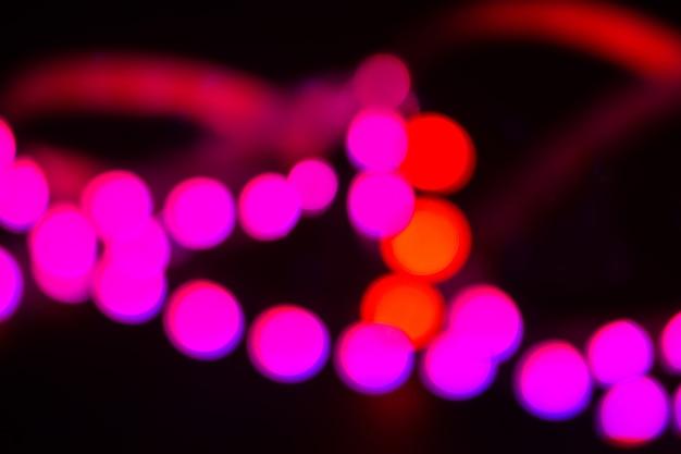 デュオトーン赤と紫のネオンが黒に点灯します。抽象的なぼやけた背景。