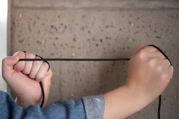 Прочный, не разрывающийся прорезиненный шнур в женских руках