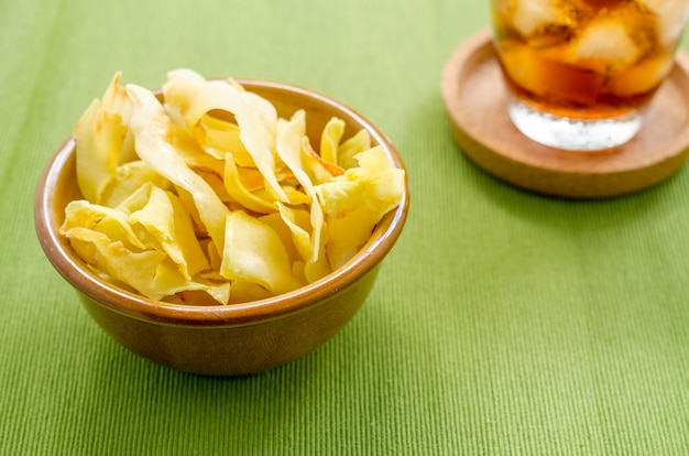 Durian chips fried snack fruit in brown blow on green background