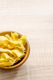 Durian chips fried snack fruit in brown blow on wooden background