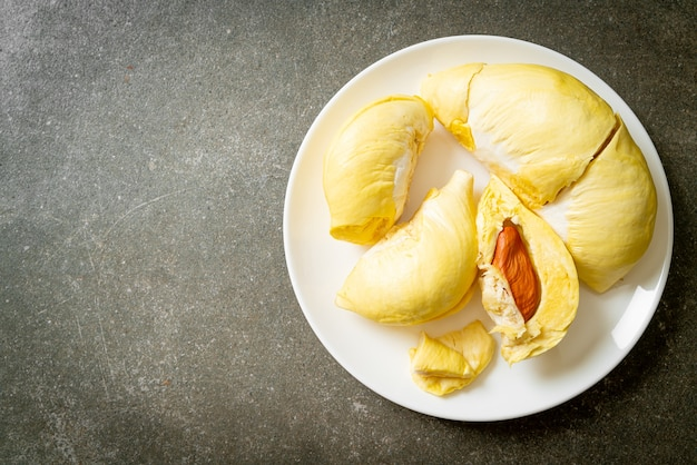 Дуриан спелый и свежий, кожура дуриана на белой тарелке