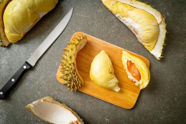 Дуриан спелый и свежий, кожура дуриана на деревянной доске