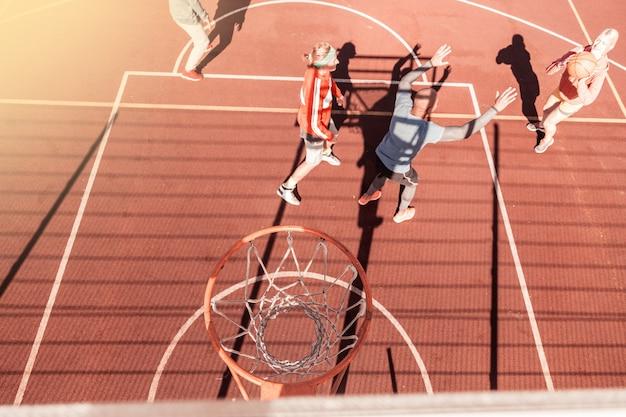 試合中。その下で遊んでいる人々とバスケットボールのバスケットの上面図