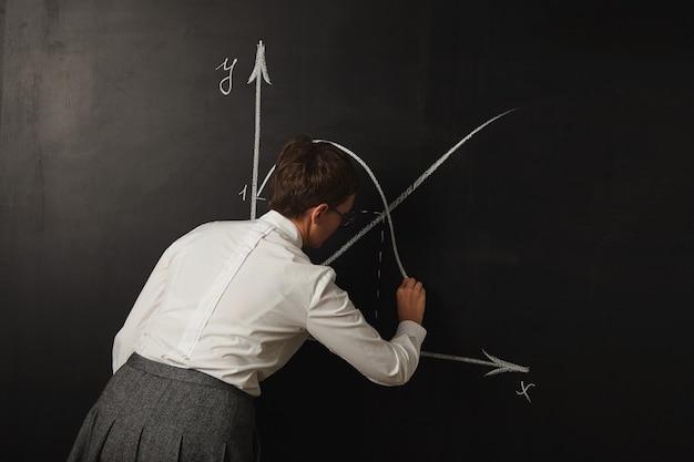 Во время урока математики учитель в консервативной одежде рисует на доске графики белым мелом.