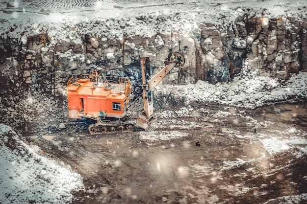 강설량 동안 겨울에 화강암 채석장에 있는 큰 거대한 노란색 굴착기. 겨울날 그의 경력에 눈이 흩뿌려진 화강암 바닥에 거대한 적재 삽 양동이가 서 있다