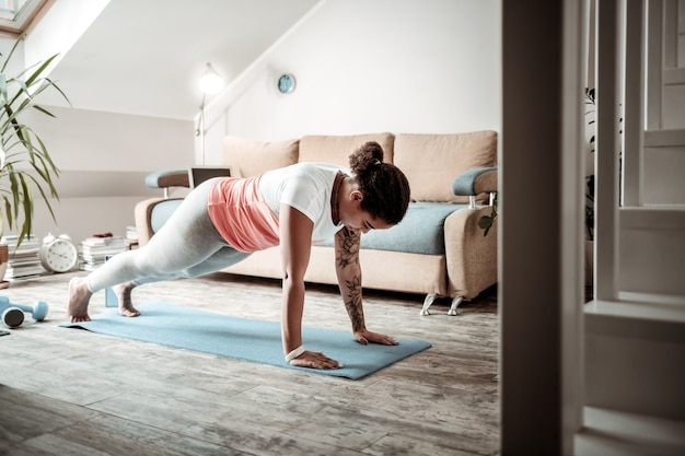 アクティブなトレーニング中。家の1階でトレーニング中に腕立て伏せをしている集中した若い女性