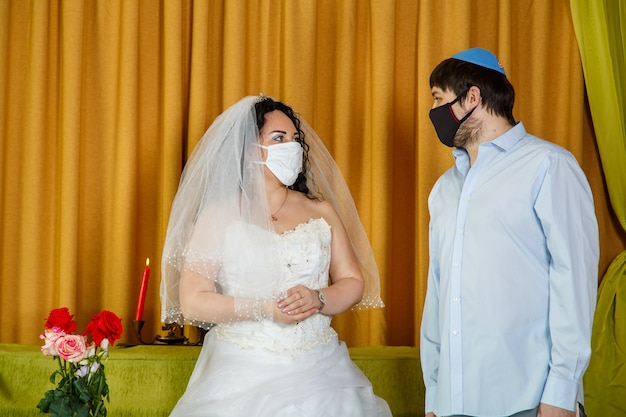 During the chupa ceremony in the synagogue, the masked jewish bride and groom stand side by side. horizontal photo.