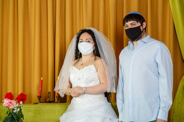 During the chupa ceremony in the synagogue, the masked jewish bride and groom stand side by side. horizontal photo