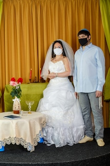 During the chupa ceremony in the synagogue, the masked jewish bride and groom stand side by side. vertical photo