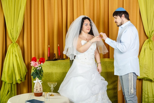 During a chuppah ceremony at a jewish synagogue wedding, the groom puts a ring on the bride's index finger. horizontal photo