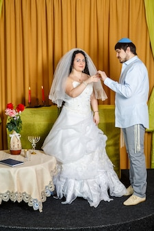 During a chuppah ceremony at a jewish synagogue wedding, the groom puts a ring on the bride's index finger. vertical photo