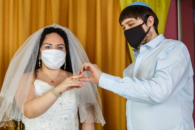 During a chuppah ceremony at a jewish wedding in a synagogue, the groom puts a ring on the bride's index finger of a masked newlywed couple. horizontal photo.