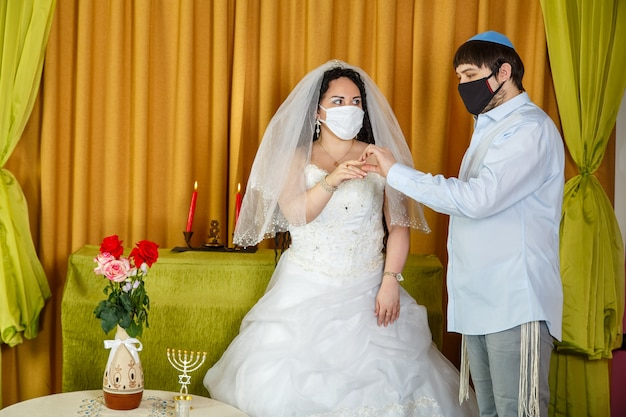 During a chuppah ceremony at a jewish wedding in a synagogue, the groom puts a ring on the bride's index finger of a newlywed couple wearing a pandemic mask. horizontal photo