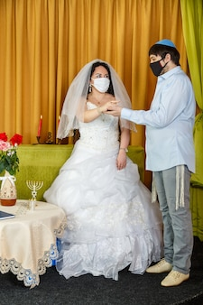 During a chuppah ceremony at a jewish wedding in a synagogue, the groom puts a ring on the bride's index finger while wearing a protective mask. vertical photo