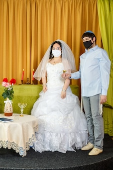 During the chuppah ceremony in the synagogue, the bride and groom stand next to the groom holding a glass of wine in the hand of the newlyweds in a protective mask. vertical photo