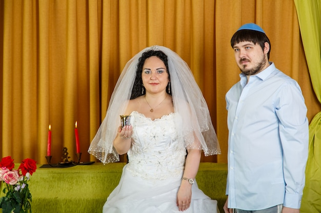 During the chuppah ceremony in the synagogue, the bride holds a glass of wine in her hand, the groom stands nearby. horizontal photo