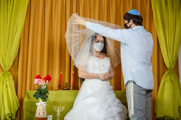 During the chuppah ceremony in the synagogue, the masked bride and groom lifts the veil from the bride's face. horizontal photo