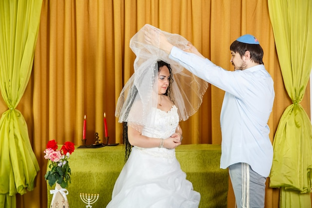 During the chuppah ceremony at a synagogue wedding, the groom lifts the veil from the bride's face. horizontal photo