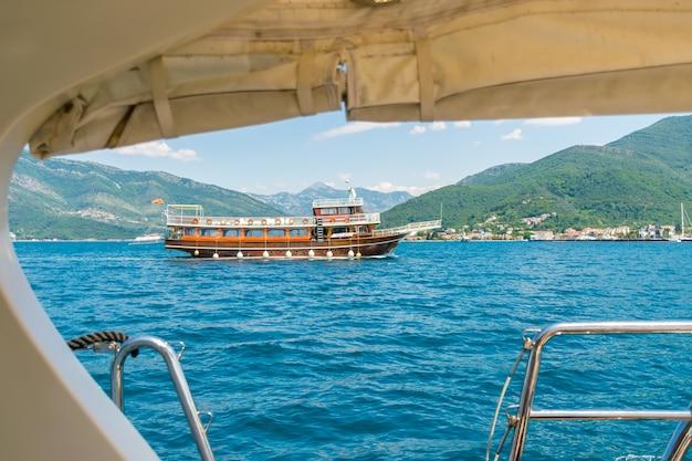 During good weather, tourists on yachts stroll along the boka-kotorska bay.