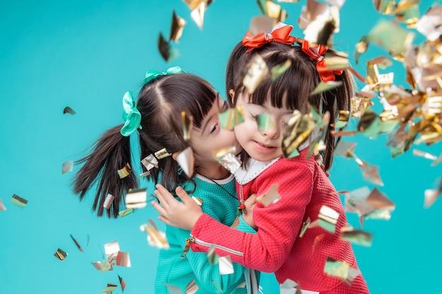 ホリデーシーズン中。紙吹雪の流れの下に立っている間、黒髪のポジティブな姉妹がお互いにキスしている