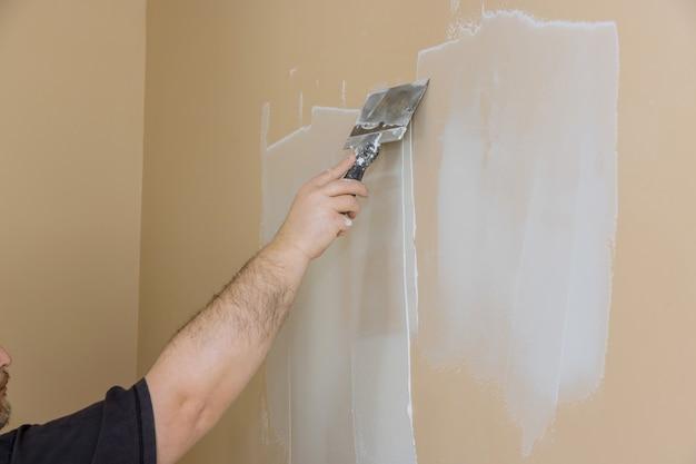 Во время ремонта комнаты рабочий оштукатурил стену из гипсокартона.