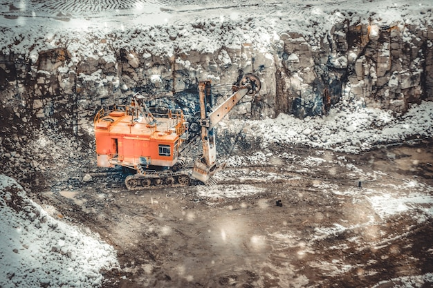 During a snowfall big huge yellow excavator in a granite quarry in winter. huge loading shovel bucket stands on a granite floor strewn with snow in his career on a winter day