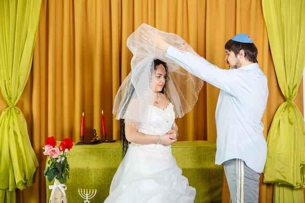 Во время церемонии хупы на свадьбе в синагоге жених приподнимает вуаль с лица невесты. горизонтальное фото