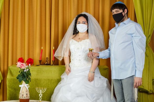 シナゴーグでのフッパーセレモニーでは、新郎が花嫁の隣に立ってグラスワインを持っています。
