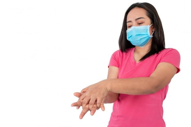 Во время эпидемии коронавируса (covid-19) женщина моет руки спиртовым гелем на белом фоне.