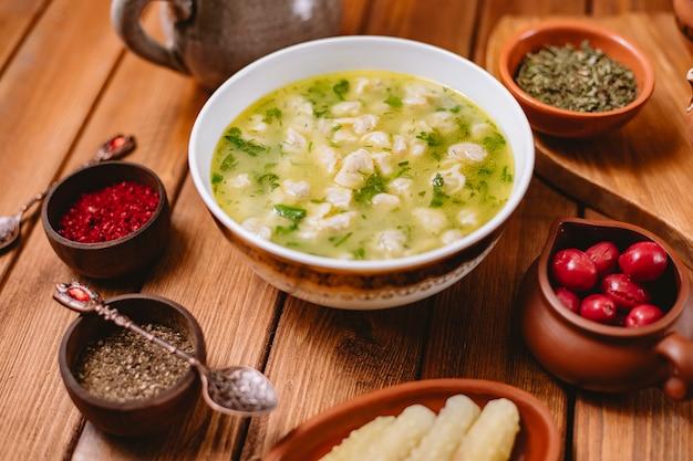 Zuppa di gnocchi di dushbara servita con erbe secche e spezie orizzontali