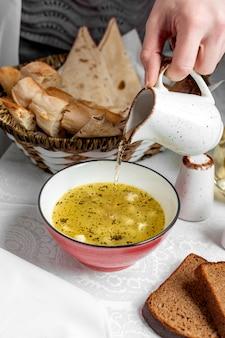 酢の物を注いだ乾燥ミントをまぶしたスープのドシュバラ