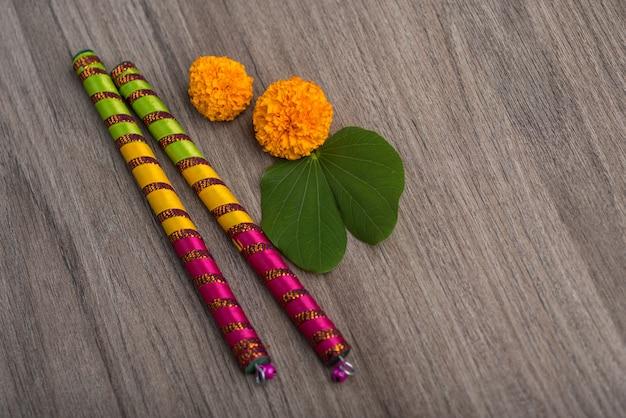 インドの祭りdussehraとnavratriandマリーゴールドの花と木製の背景にdandiyaスティック