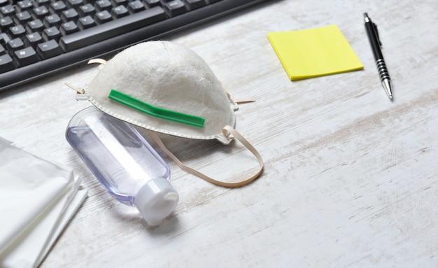 キーボードと黄色のメモ用紙の横にある机の上の顔と手の消毒剤のボトルをペンで保護するダストマスク