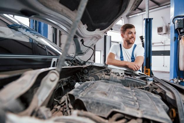 エンジンのほこり。自動車のサロンで働く青い制服を着た従業員