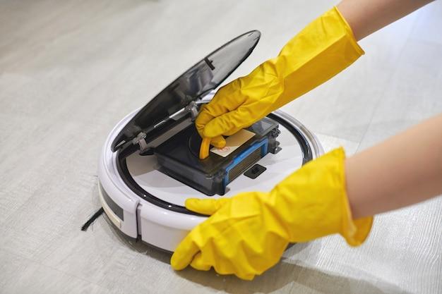 手袋をはめた手にロボット掃除機のダスト収納ボックスケース。ほこりや破片を収集するためにフィルターとコンテナを挿入する女性