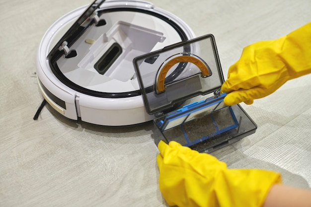 Dust storage box case of robotic vacuum cleaner in gloved female hands. woman in protective gloves taking out container and filter to clean it from dirt and debris