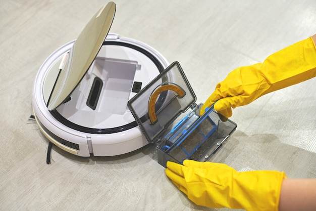 Dust storage box case of robotic vacuum cleaner in gloved female hands.