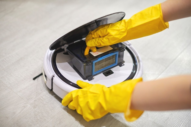 Dust storage box case of robotic vacuum cleaner in gloved hands