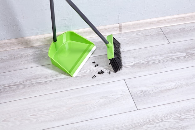 Dustpan and brush  made of plastic are cleaning floor in room from dust and trash.