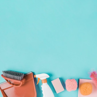 Dustpan, spray bottle and scrub on turquoise background