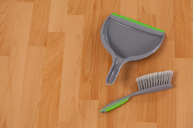 Dustpan and sweeping brush on wooden floor