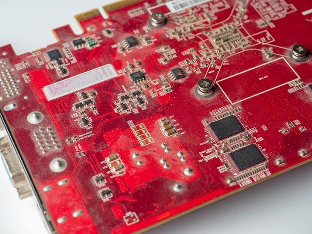 빨간 칩이 있는 먼지가 많은 인쇄 회로 기판. 오래된 비디오 카드