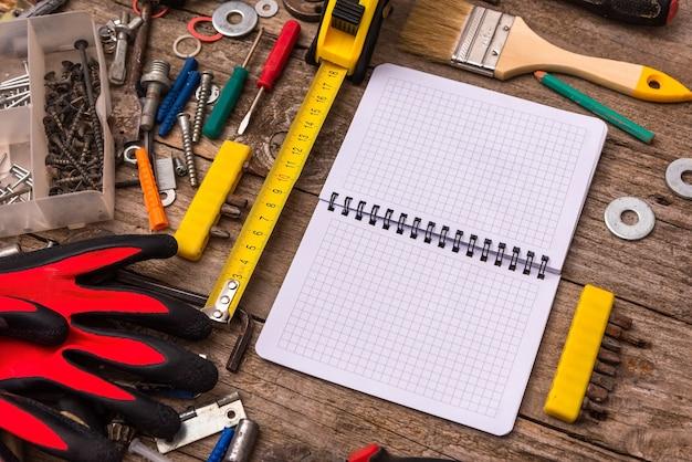 ほこりっぽいツールと木製のテーブルのメモ帳。