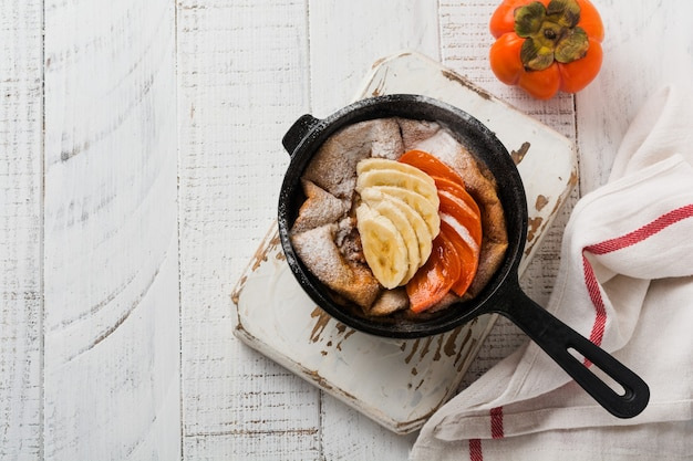 Голландский блинчик с яблоком, хурмой, бананом, корицей в небольшой железной сковороде на поверхности деревянного стола. вид сверху.